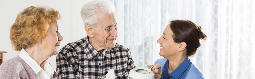 older senior couple talking to woman
